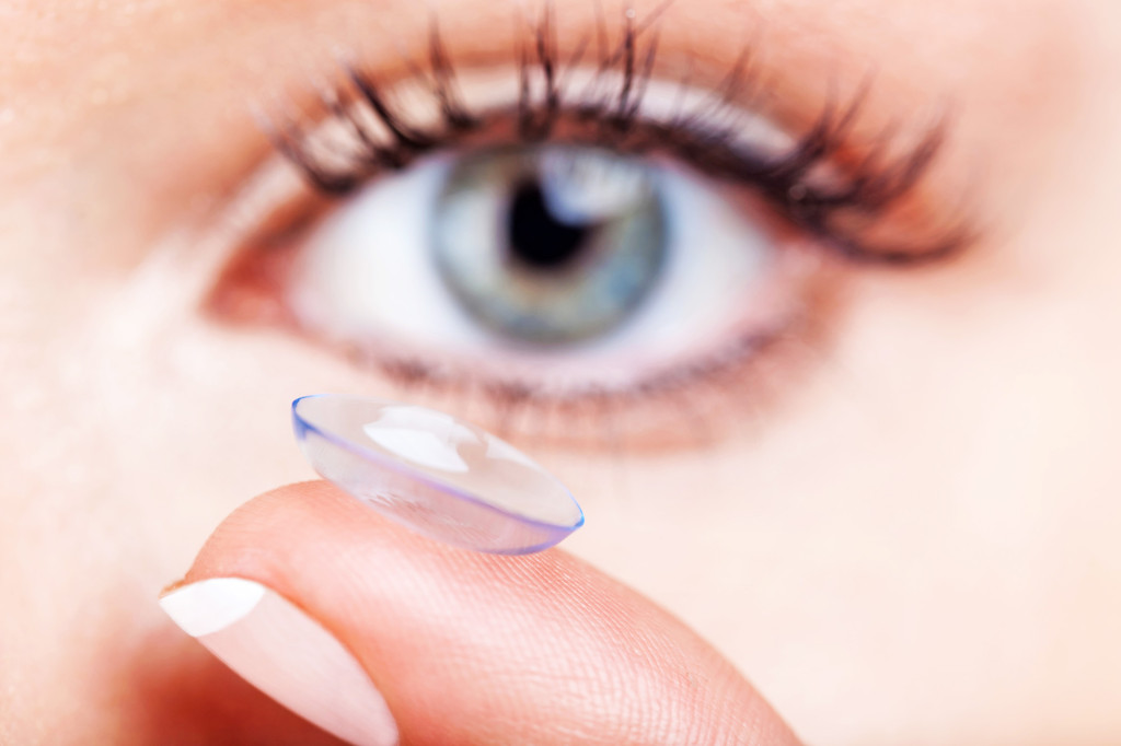 Woman eye with contact lens applying